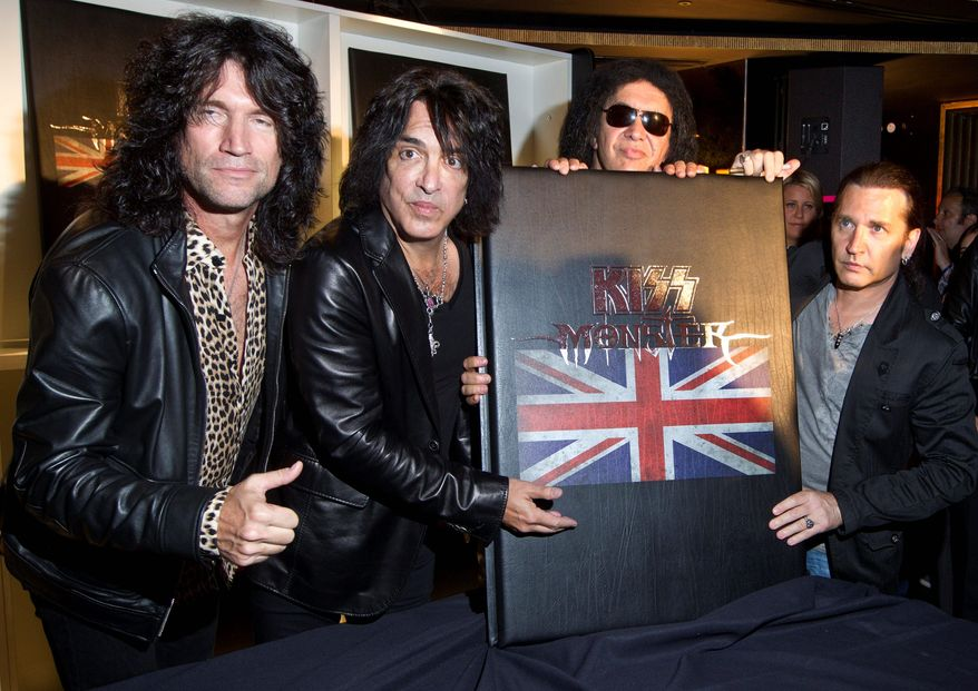 "**FILE** Rock band Kiss members (from left) Tommy Thayer, Paul Stanley, Gene Simmons and Eric Singer hold their book ""Monster,"" which contains photographs of the band's 40-year career, at a July 3, 2012, press conference in London. (Associated Press)"
