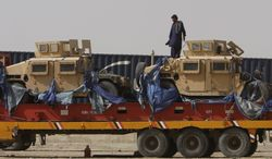 A man Wednesday stands on a truck carrying NATO vehicles in Chaman, Pakistan, near the Afghan border. Pakistan on Tuesday decided to end a seven-month blockade of NATO troop supplies in a rare bright spot in relations with the United States. (Associated Press)
