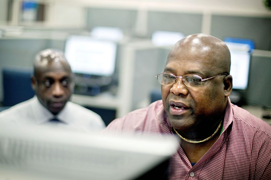 Army veteran Chester Dixon (right) works with William Moore, a Georgia Department of Labor veterans representative, to apply for a new skills-based program to get out-of-work veterans trained and back into the job market in Atlanta. (Associated Press)