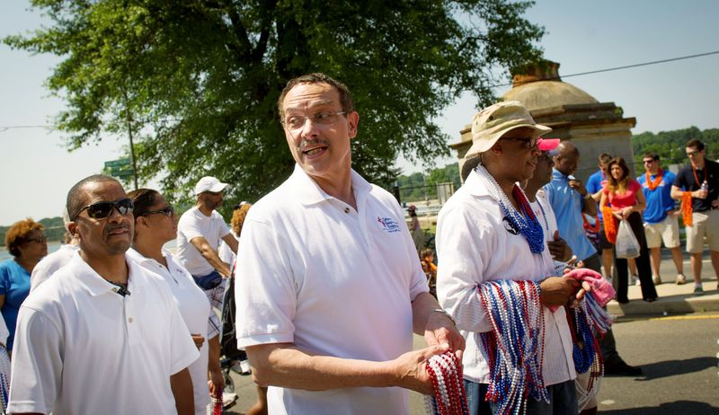 D.C. Mayor Vincent C. Gray carries throws for people in the crowd as he begins his walk in the 46th Annual Palisades Parade and Picnic in Washington on Wed