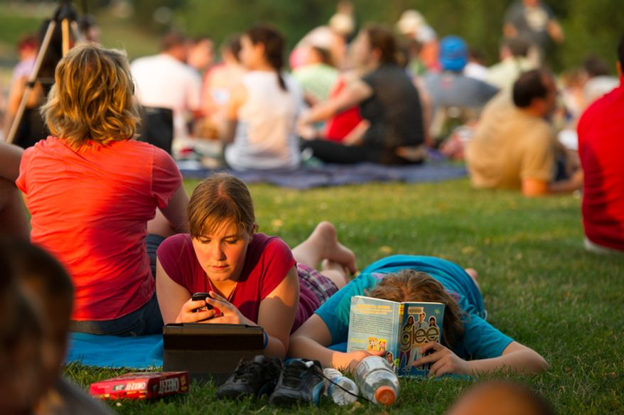 Madeline Ray, 13, left, and her sister Natalie, 12, right, of Lafayette, Ind., keep themselves occupied on grass near the Iwo Jima Memorial a few hours before fireworks are set to explode over the National Mall to celebrate Independence Day, Arlington, Va. (Andrew Harnik/The Washington Times)