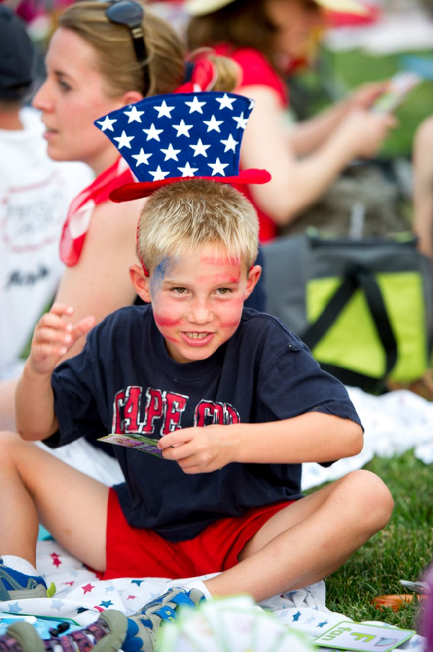 Graham Haberl, 6, of McLean, Va., plays card games with family a the lawn near the Iwo Jima Memorial a few hours before fireworks are set to explode over the National Mall to celebrate Independence Day, Arlington, Va. (Andrew Harnik/The Washington Times)