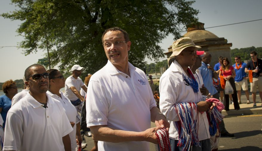 D.C. Mayor Vincent C. Gray carries throws for people in the crowd as he begins his walk in the 46th Annual Palisades Parade and Picnic. (Rod Lamkey Jr./The Washington Times)