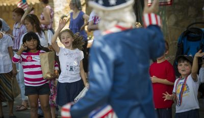 Grant Berning, of Dunn Loring, Va., plays the part of Uncle Sam and is greeted by the crowd as he marches in the 46th Annual Palisades Parade and Picnic. (Rod Lamkey Jr./The Washington Times)