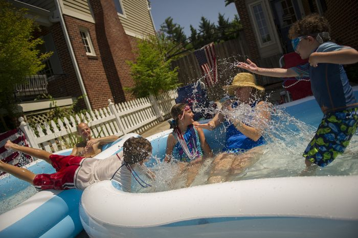 Susan Ettinger (second from right) gets splashed with water from her son Sam, 5, (right) daughter Sarah, 8, (second from left) and son Jack, 7, (left) while her husband Jason relaxes in the background as they enjoy the cool water of their front yard pools and watch the passing of the 46th Annual Palisades Parade and Picnic in Washington, D.C., Wednesday, July 4, 2012. (Rod Lamkey Jr./The Washington Times)