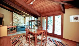The dining room has hardwood flooring, a cathedral ceiling and French doors that lead onto the deck. It opens into the two-story living room.