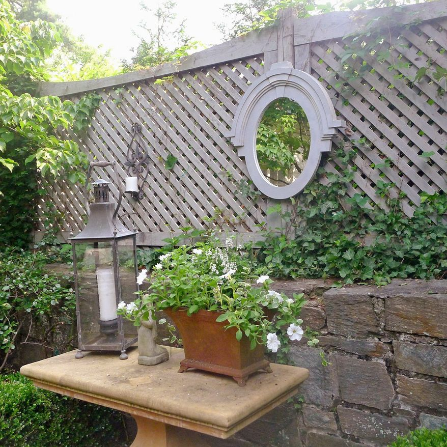 Photo courtesy of kelley interior design Kelley Proxmire of Kelley Interior Design in Bethesda suggests using a mirror on an outdoor fence or various groupings of potted plants to add interest to a patio or deck.