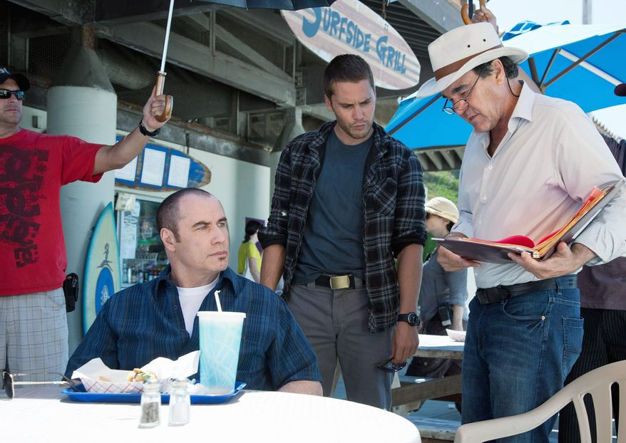 """Actors John Travolta (left) and Taylor Kitsch (center) confer with director Oliver Stone during the filming of """"Savages.""""The movie, which opens Friday, also stars Salma Hayek and Benicio Del Toro. (Universal Pictures)"""