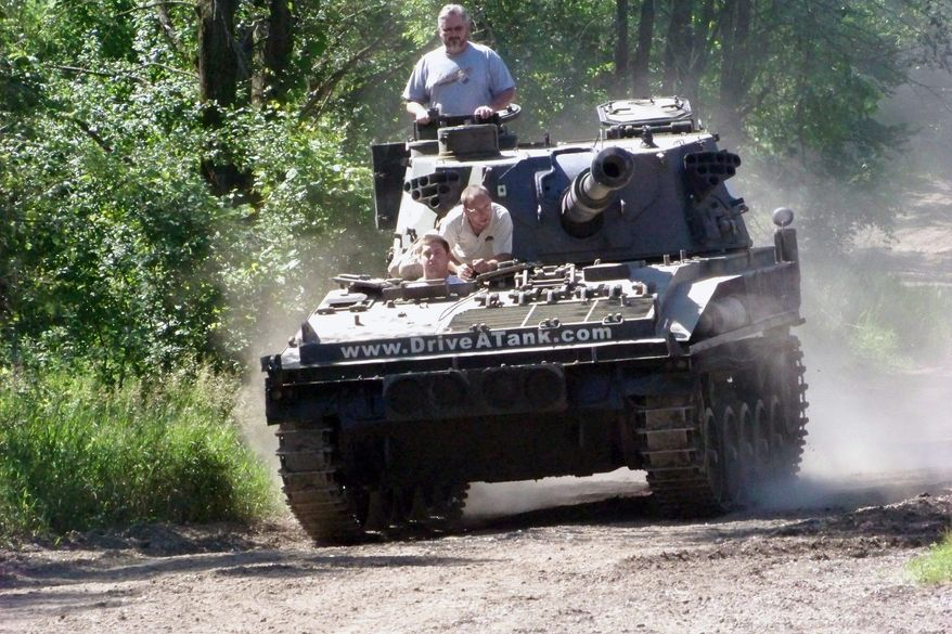 Nick Walker takes the controls while his father, Brad, looks out from the turret. 'Drive-a-Tank' owner Tony Borglum goes along for the ride. (Associated Press)