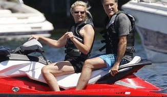 Republican presidential candidate Mitt Romney and his wife, Ann, jet-ski on Lake Winnipesaukee in Wolfeboro, N.H., on Monday, July 2, 2012. The Romneys have a vacation home there. (AP Photo/Charles Dharapak)