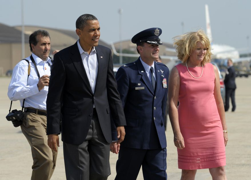 President Obama walks with Col. Ken Rizer and his wife, Cheri, before boarding Air Force One at Andrews Air Force Base in Maryland on July 5, 2012. Obama is heading to Ohio and Pennsylvania for a campaign bus trip. (Associated Press)