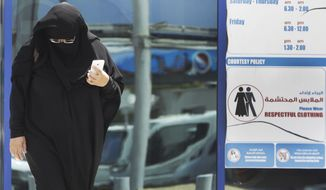 ** FILE ** In this photo taken Monday, June 25, 2012, a muslim Emirati woman passes by a dress code sign at a shopping mall in Dubai, United Arab Emirates. (AP Photo/Kamran Jebreili)