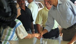 President Obama shakes hands July 6, 2012, with waitress Toni Watkins during a stop at Ann's Place in Akron, Ohio, during his two-day campaign bus trip through Ohio and Pennsylvania. Watkins, a 23-year employee at the restaurant, took the president's order and served him breakfast. (Associated Press/Akron Beacon Journal)