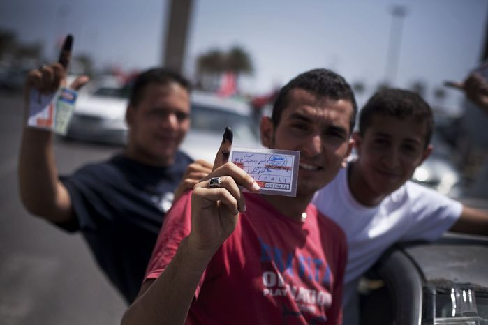 Libyan men hold their elections ID cards while celebrating election day in Tripoli, Libya, Saturday, July 7, 20