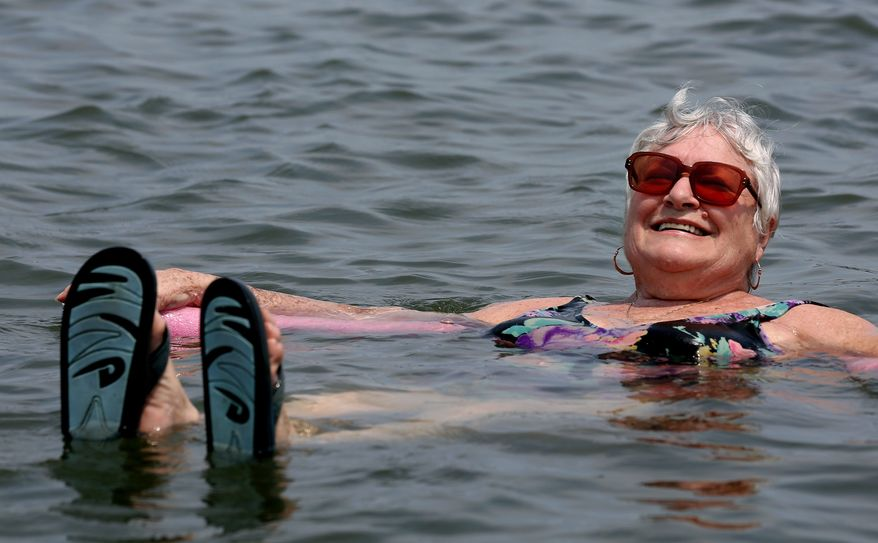 Lillian Mariscalo of Oyster Bay, N.Y., cools off in the waters of an Oyster Bay beach on Long Island's North shore Saturday, July 7, 2012. The heat gripping much of the country was set to peak Saturday in several places, with temperatures of more than 100 degrees expected in Philadelphia, excessive heat warnings in the Midwest and ongoing power outages of more than a week in the mid-Atlantic. (AP Photo/Craig Ruttle)
