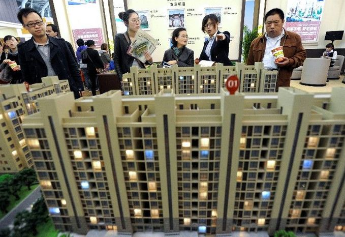 People attend a real estate fair in Nanjing, China, earlier this year. China's economy may slow further despite stimulus measures, Premier Wen Jiabao said Sunday. A rise in real estate prices, driven in part by government stimulus spending and bank lending, has fueled political tensions. (Associated Press)