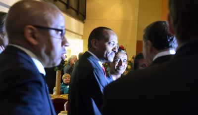 Ethiopian Ambassador to the U.S. Girma Birru (center) chats with then-Metropolitan Washington Airports Authority Vice Chairman Leonard Manning in March at the embassy. In his MWAA role, Mr. Manning helped facilitate opening the U.S. market to Ethiopian roses. (Jessica Carpenter/The Washington Times)