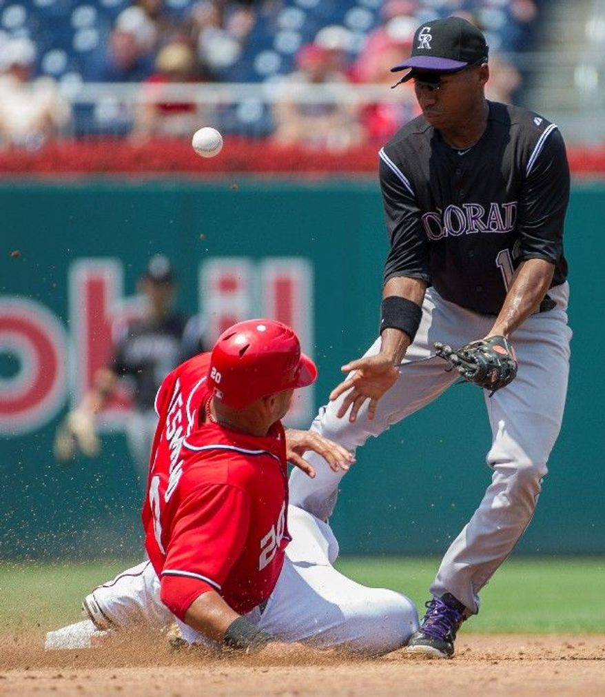 Nationals Ian Desmond (20) is safe stealing second base as Rockies Jonathan Herrerabobles the ball in the bottom of the second inning as the Washington Nationals host the Colorado Rockies at Nationals Park in Washington, D.C., Sunday, July 8, 2012. (Rod Lamkey Jr./The Washington Times)
