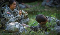 "Sapper candidate Army Capt. Stephanie Godman takes her turn at lunch as she eats a military Meal Ready to Eat while her ""battle buddy"" and fellow sapper candidate National Guard Staff Sgt. Anthony Hughes is posted up in a clearing to help form a perimeter to keep watch. (Rod Lamkey Jr./The Washington Times)"