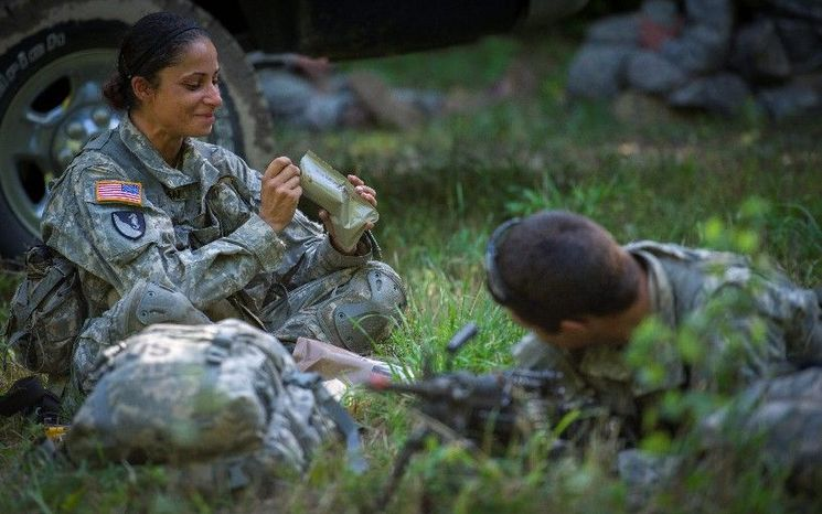 """Sapper candidate Army Capt. Stephanie Godman takes her turn at lunch as she eats a military Meal Ready to Eat while her """"battle buddy"""" and fellow sapper candidate National Guard Staff Sgt. Anthony Hughes is posted up in a clearing to help form a perimeter to keep watch. (Rod Lamkey Jr./The Washington Times)"""