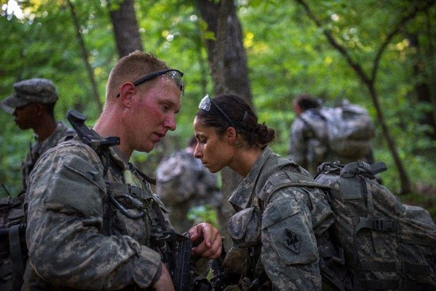 Army Capt. Stephanie Godman confers with another sapper candidate as they plan to head off on a mission during another day of training at Fort Leonard Wood in Missouri. (Rod Lamkey Jr./The Washington Times)