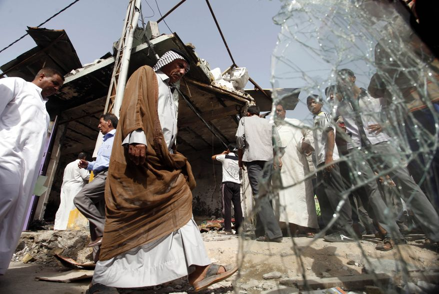 People inspect a bomb scene on July 4, 2012, a day after an explosives-laden vegetable truck ripped through a crowded market in Diwaniyah, 80 miles (120 kilometers) south of Baghdad. (Associated Press)