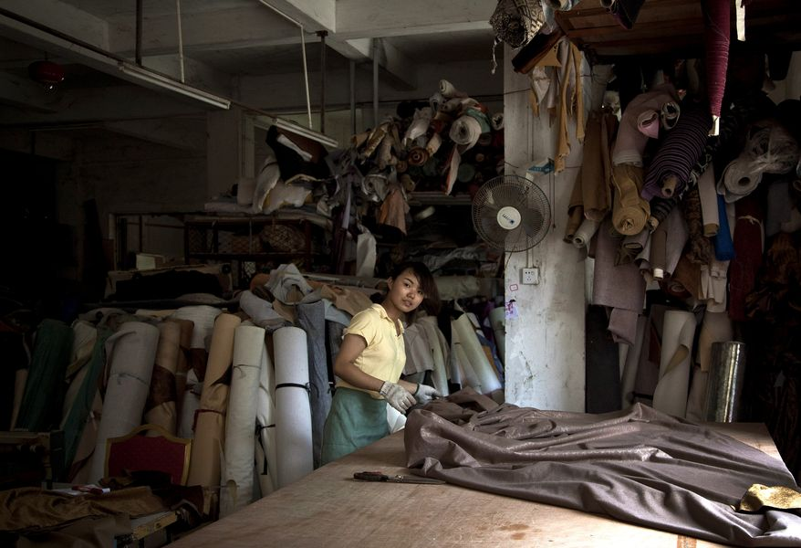 A worker lays out fabric June 29, 2012, at a local furniture manufacturing factory in Zhanjiang, China. (Associated Press)