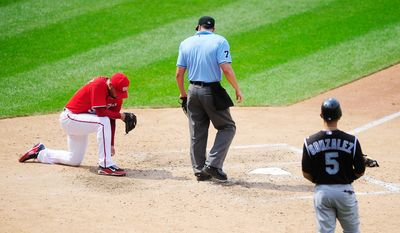 Michael Gonzalez, far left, takes a moment to collect himself after the Rockies scored to tie the game on a wild pitch at Nationals Park.  (Ryan M.L. Young/The Washington Times)