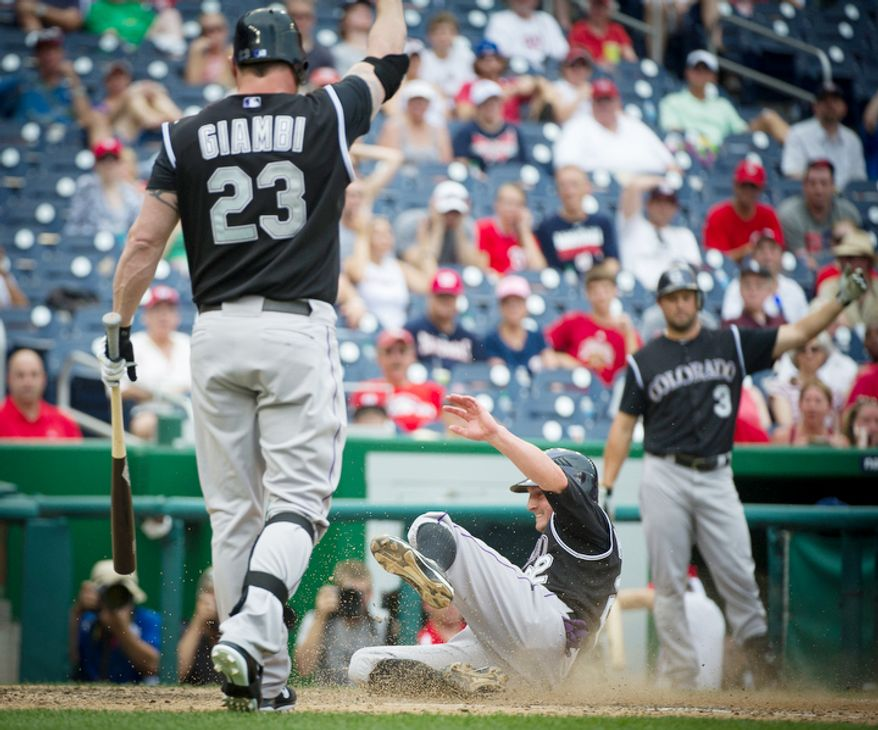 Rockies Jordan Pacheco (22) slides safely into home on a wild pitch and scores what would be the winning run as the Washington Nationals host the Colorado Rockies. The Rockies defeated the Nationals 4-3. (Rod Lamkey Jr./The Washington Times)