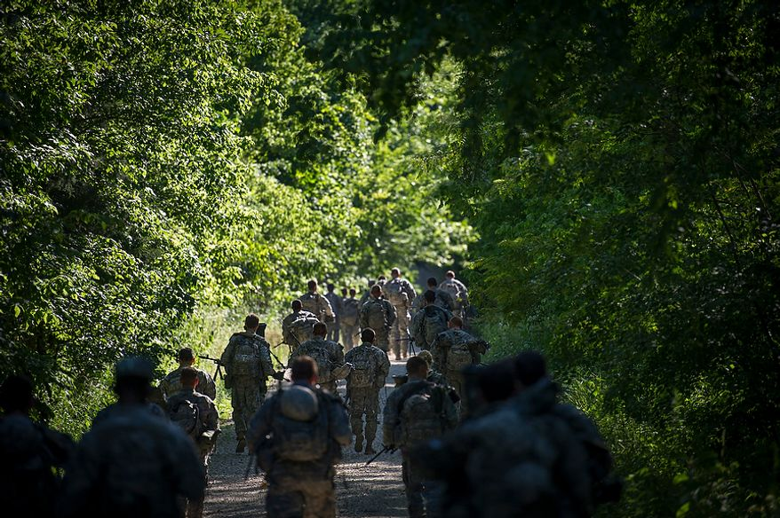 Following a brief meal the platoon makes it's way along a dusty gravel road to their next mission, during another day of Sapper School training at U.S. Army Maneuver Support Center (MANSCEN) and Fort Leonard Wood in Fort Leonard Wood, Mo., Tuesday, June 26, 2012. (Rod Lamkey Jr./The Washington Times)