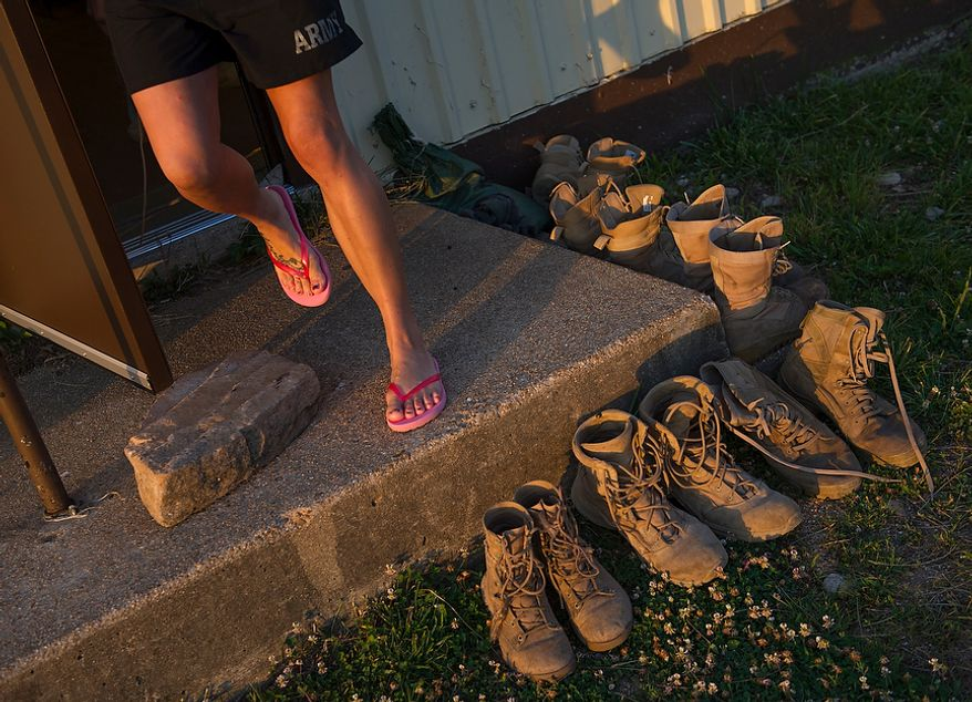 Army Capt. Stephanie Godman, a Sapper candidate, wears her pink flip-flops as she steps past boots on her way to the shower after spending her first night in an actual bed in the co-ed barracks after two grueling weeks in the field, at the U.S. Army Maneuver Support Center (MANSCEN) at Fort Leonard Wood, Mo., on Thursday, June 28, 2012. (The Washington Times)