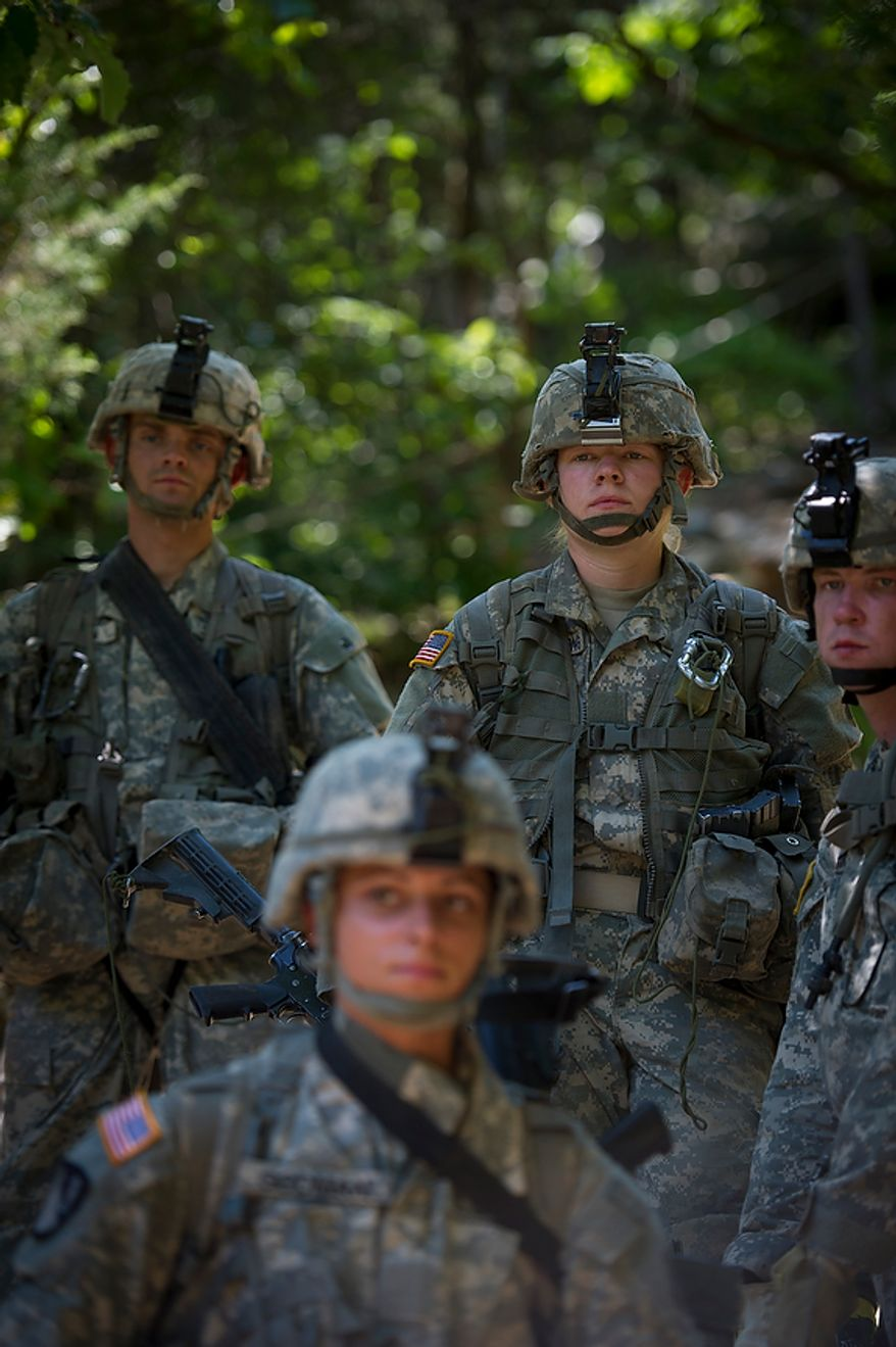 Sapper candidates and Army Captains Stephanie Godman (bottom) and Aston Armstrong (top) listen to instructions as they prepare for a mission to repel down the side of a cliff during another day of Sapper School training at U.S. Army Maneuver Support Center (MANSCEN) and Fort Leonard Wood in Fort Leonard Wood, Mo., Tuesday, June 26, 2012. (Rod Lamkey Jr./The Washington Times)