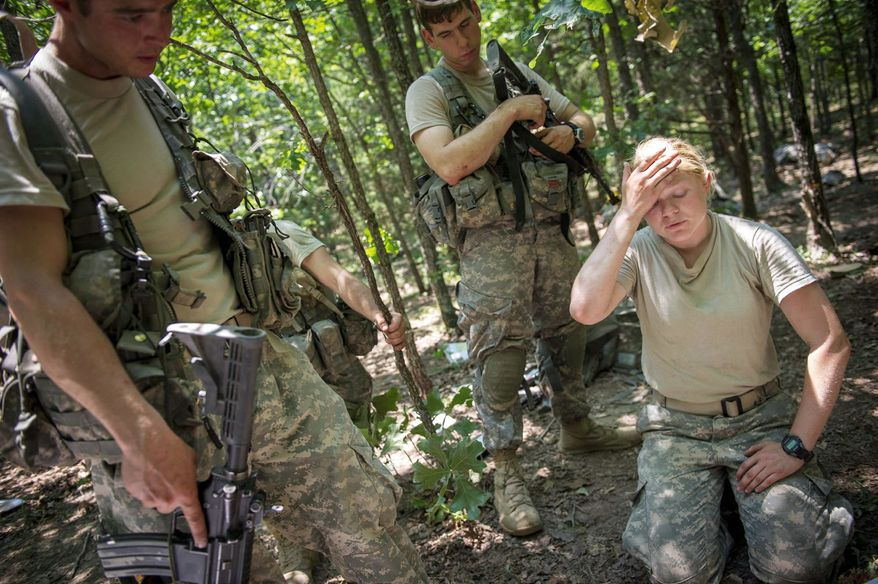 With temperatures on the Missouri training course in the triple digits, Capt. Aston Armstrong wipes the sweat from her face during a break as she confers with Army Staff Sgt. Rock Richardson (left) and Army Capt. Pablo Diaz to prepare her platoon for the next mission. (Rod Lamkey Jr./The Washington Times)