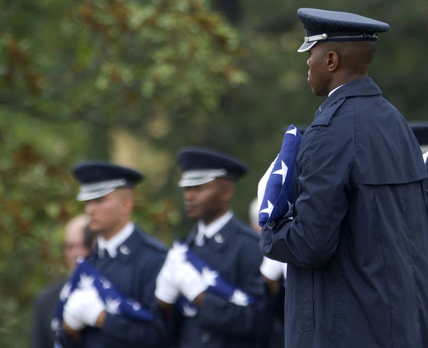 Members of the Air Force Honor Guard hold American flags to be presented to family members during a burial service July 9, 2012, at Arlington National Cemetery in Arlington, Va., for six men killed in 1965 when an Air Force plane carrying the men crashed after leaving Vietnam for a combat mission.