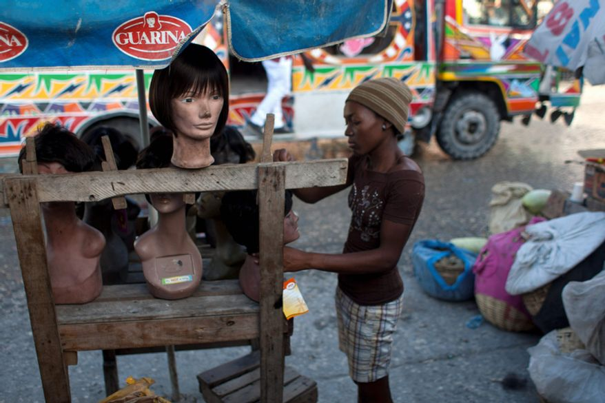 Judeline Andre, 17, works at a street stall with model heads displaying wigs and hairpieces at the landmark Iron Market in Port-au-Prince, Haiti that was damaged by the 2010 earthquake.  (AP Photo/Dieu Nalio Chery)