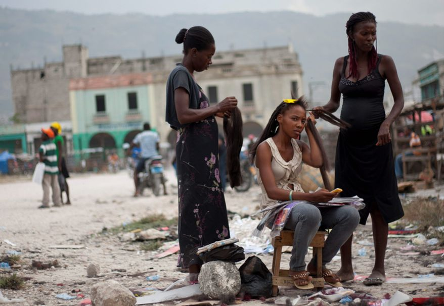 A woman gets her hair combed by hairdressers on a street in downtown Port-au-Prince, Haiti. After Haiti's devastating January 2010 earthquake, dozens of independent hair stylists that braided and colored hair in the capital's Iron Market moved their activities to the streets, where they resumed their businesses not long after the disaster. (AP Photo/Dieu Nalio Chery)