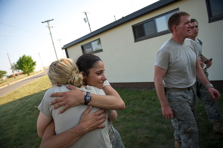 Sapper candidates and Army Captains Aston Armstrong (left) and Stephanie Godman (right) hug, cry and laugh after learning they both made the cut at the conclusion of the grueling of Sapper School training course at U.S. Army Maneuver Support Center (MANSCEN) and Fort Leonard Wood in Fort Leonard Wood, Mo., Wednesday, June 27, 2012. (Rod Lamkey Jr./The Washington Times)