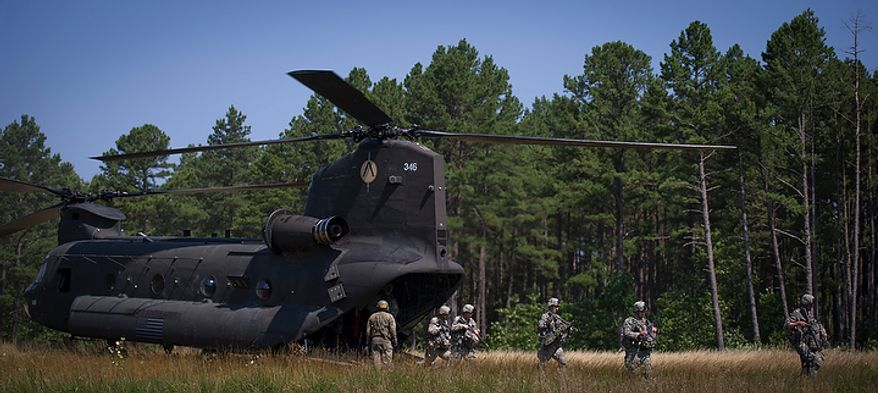 A portion of the Sapper platoon makes their way through tall grass after arriving on a Chinook helicopter, en route to a base for the planning of a mission, during another day of Sapper School training at U.S. Army Maneuver Support Center (MANSCEN) and Fort Leonard Wood in Fort Leonard Wood, Mo., Wednesday, June 27, 2012. (Rod Lamkey Jr./The Washington Times)