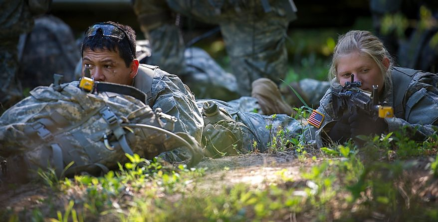 """Sapper candidate and Army Captain Aston Armstrong (right) is posted up next to her """"Battle Buddy"""" Army SFC Jonathan Guerrero (left) in a clearing during a break to eat a meal during another day of Sapper School training at U.S. Army Maneuver Support Center (MANSCEN) and Fort Leonard Wood in Fort Leonard Wood, Mo., Tuesday, June 26, 2012. (Rod Lamkey Jr./The Washington Times)"""