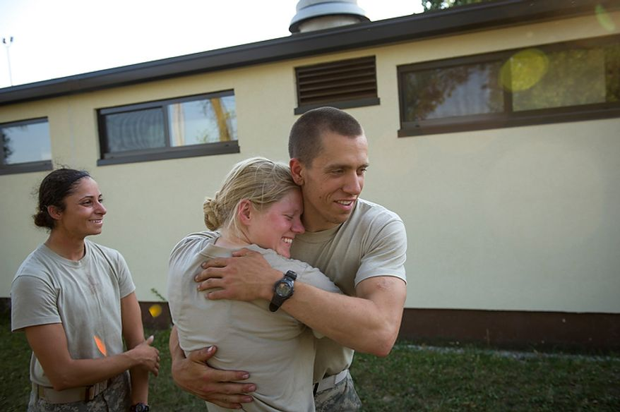 Sapper candidate and Army Captain Aston Armstrong gets a hug from Army Captain John Todd, a fellow Sapper who also passed as her friend, Sapper candidate and Army Captain Stephanie Godman (left) also celebrates their success as they hug, cry and laugh after learning they both made the cut at the conclusion of the grueling of Sapper School training course at U.S. Army Maneuver Support Center (MANSCEN) and Fort Leonard Wood in Fort Leonard Wood, Mo., Wednesday, June 27, 2012. (Rod Lamkey Jr./The Washington Times)
