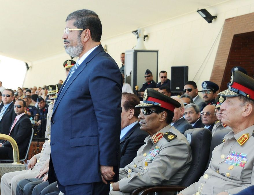 Egyptian President Mohammed Morsi (left) joins Field Marshal Hussein Tantawi (center) and Chief of Staff Sami Anan (right) at a ceremony at an air force base in Cairo on Tuesday. Egypt's Islamist-dominated parliament opened a new front in the country's leadership showdowns Tuesday by meeting in defiance of orders that disbanded the chamber and brought Mr. Morsi in conflict with both the powerful military and the highest court. (Associated Press)