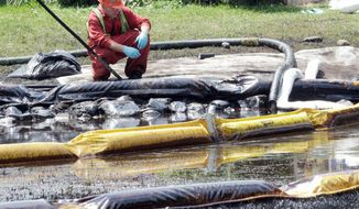 A worker monitors water in Talmadge Creek in Marshall Township, Mich., near the Kalamazoo River in 2010 as oil from a ruptured pipeline, owned by Enbridge Inc., is trapped by booms. Federal investigators said Tuesday that the Canadian company should be held responsible. (Associated Press)