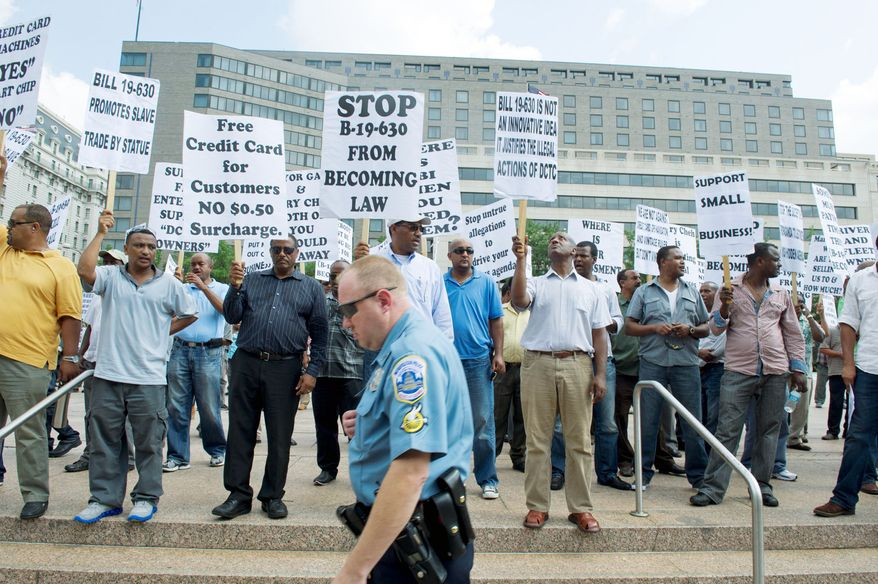 Taxicab drivers demonstrate Tuesday in Freedom Plaza against a bill that, among its provisions, requires cabs to have credit card readers and new meters that provide printed receipts. The D.C. Council passed the bill. (Barbara L. Salisbury/The Washington Times)