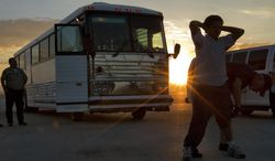 **FILE** An illegal immigrant from El Salvador is searched June 26, 2012, on the tarmac at Phoenix-Mesa Gateway Airport in Mesa, Ariz., as the sun rises prior to boarding an MD-80 aircraft for a repatriation flight of 80 immigrants to their home country. (Associated Press)