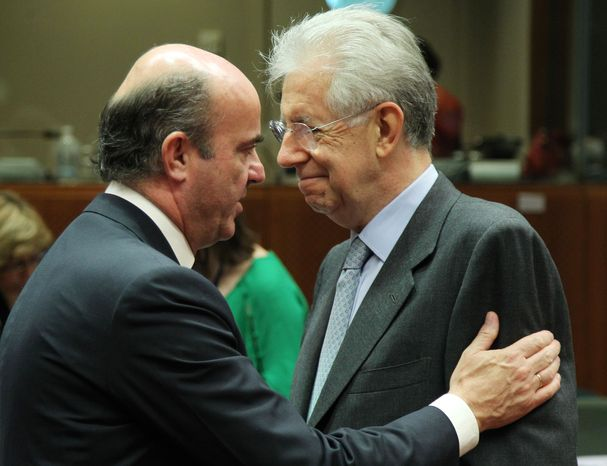 Italian Finance Minister Mario Monti (right) talks with Spanish Finance Minister Luis de Guindos Jurado during the meeting of European Union finance ministers in Brussels on Tuesday, July 10, 2012. (AP Photo/Yves Logghe)