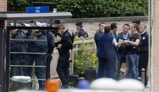 Police surround a school complex where an armed man took hostages on Tuesday, July 10, 2012, in Vitry sur Seine, France, south of Paris. (AP Photo/Jacques Brinon)