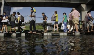 **FILE** Pedestrians use an elevated makeshift walkway to avoid the floodwaters in Bangkok on Nov. 10, 2011. (Associated Press)