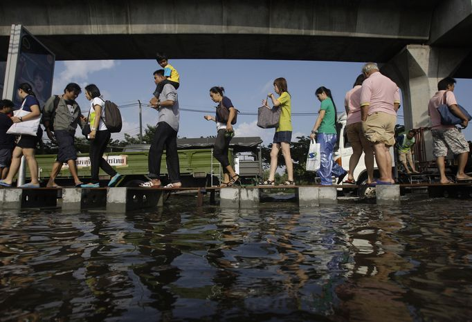**FILE** Pedestrians use an elevated makeshift walkway to avoid the floodwaters in Bangkok on Nov. 1