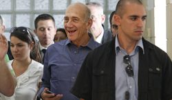 Former Israeli Prime Minister Ehud Olmert (center) leaves Jerusalem's District Court on Tuesday, July 10, 2012, following a verdict hearing at which he was cleared of the major charges in a corruption trial that forced him from power. (AP Photo/Gali Tibbon, Pool)