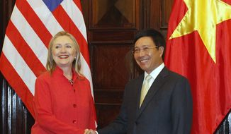 Secretary of State Hillary Rodham Clinton and Vietnamese Foreign Minister Pham Binh Minh pose for a photo at the Government Guest House in Hanoi on Tuesday, July 10, 2012. (AP Photo/Kham, Pool)